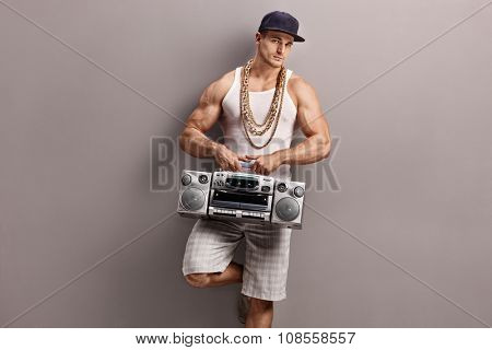 Young man in hip-hop clothes holding a ghetto blaster and leaning against a gray wall