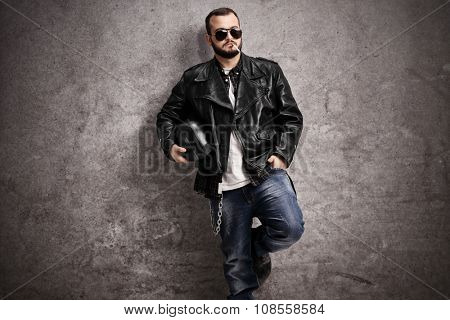 Young male biker in a leather jacket smoking a cigarette and leaning against a rusty gray wall