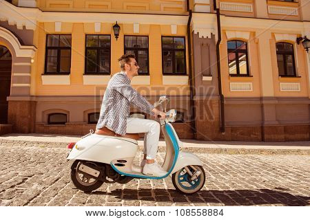 Side View Of A Handsome Cheerful Man Riding A Motorbike