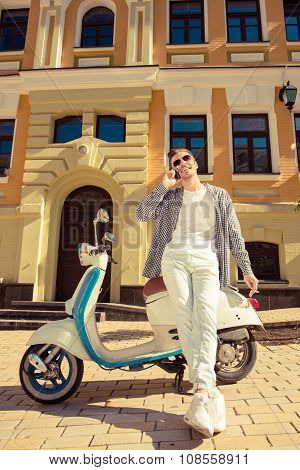 Young Handsome Man Standing Near A Motorbike Talking On The Phone