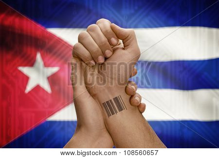 Barcode Id Number On Wrist Of Dark Skinned Person And National Flag On Background - Cuba