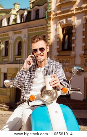 Young Handsome Man Standing Near The Scooter Holding A Cup Of Coffee Talking On The Phone