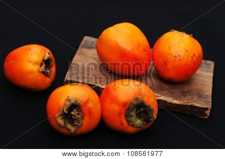 Fresh ripe persimmon on a black background, Persimmons fruit, Ripe sweet persimmons