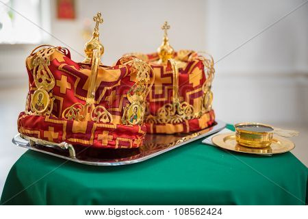 Crowns for Wedding on a silver tray and the Golden Cup of wine on the green cloth