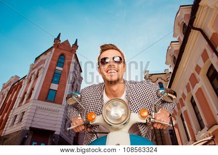 Happy Handsome Young Man With Glasses Sitting On The Motorbike