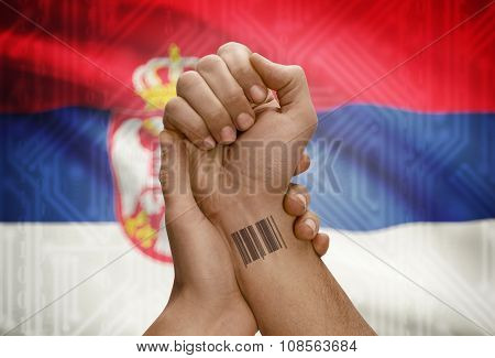 Barcode Id Number On Wrist Of Dark Skinned Person And National Flag On Background - Serbia