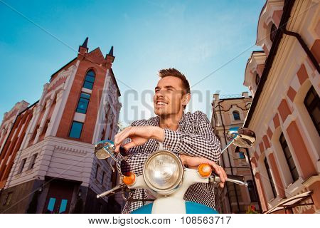 Cheerful Handsome Young Man With Glasses Sitting On The Motorbike