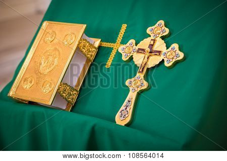 The gospel in a Golden frame and a Golden Cross on the green cloth on the stand