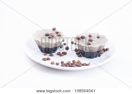 Handmade soap in the shape of muffins with coffee beans on a white plate