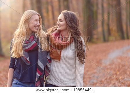 Two Female Friends Walking Through Autumn Woodland