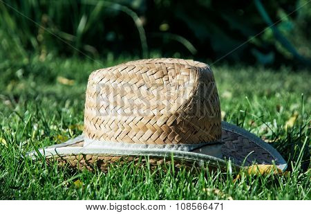 Retro Yellow Straw Hat In The Grass