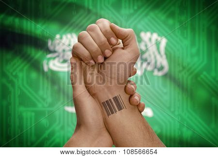 Barcode Id Number On Wrist Of Dark Skinned Person And National Flag On Background - Saudi Arabia