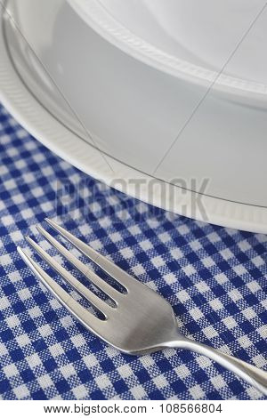 Fork And Dishes Detail Over A Blue Tablecloth
