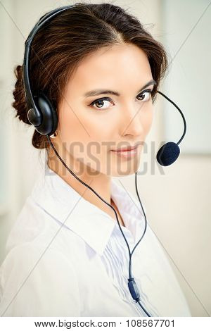 Beautiful smiling customer service woman talking on headset. Business, office life.