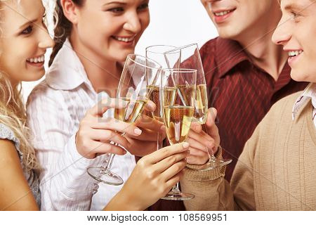 Happy men and women clinking with champagne