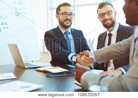 Asian businessman handshaking with partner after negotiation