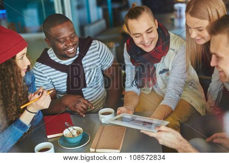 Happy guys and girls looking at touchpad held by one of friends