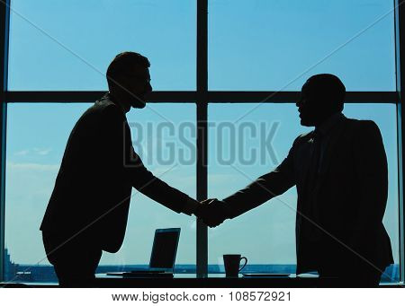 Outlines of two businessmen handshaking against window