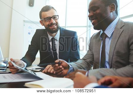 Happy businessman looking at camera during discussion of data with colleague