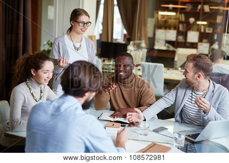 Group of young managers interacting at meeting in office