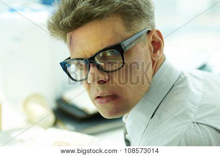 Beaten businessman in eyeglasses looking at camera