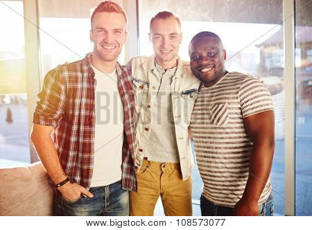 Group of friendly guys in casual-wear looking at camera