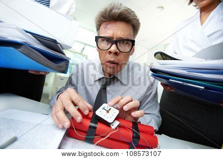 Annoyed businessman preparing dynamite while his colleagues giving him more work