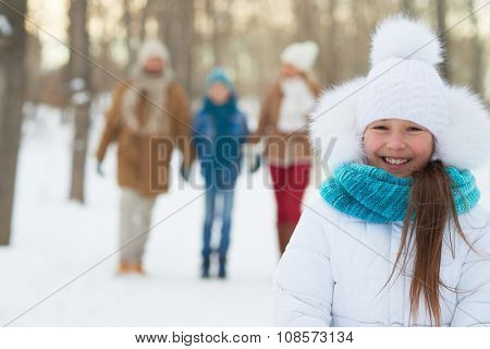 Happy girl in winterwear looking at camera with her parents and brother on background