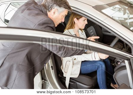 Salesman showing somethings to a customer at new car showroom