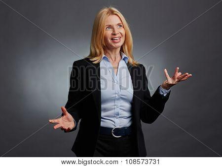 Mature businesswoman in elegant suit explaining something