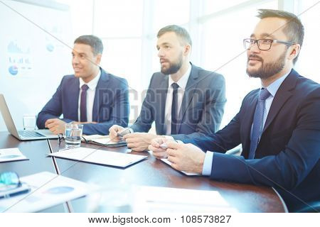 Group of successful young businessmen listening to lecture