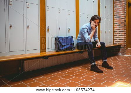 Hipster student feeling sad in hallway at the university