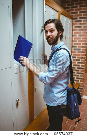 Hipster student smiling at camera in hallway at the university