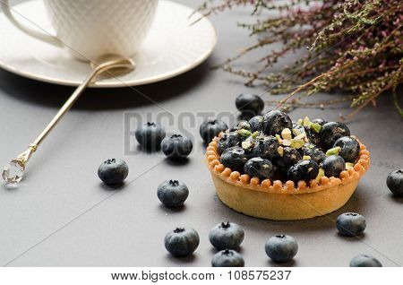 Tart With Blueberry, White Cup With Saucer On A Gray Background