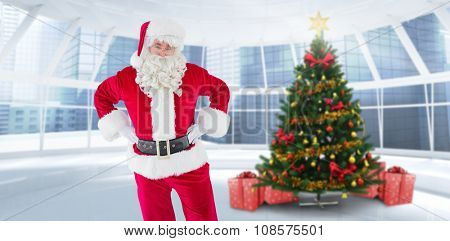 Cheerful santa claus with his hands on hips against home with christmas tree