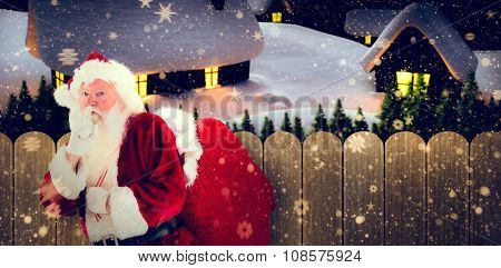 Santa asking for quiet with bag against purple sky over fence