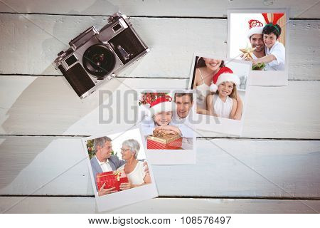 Father and son decorating Christmas tree against instant photos on wooden floor