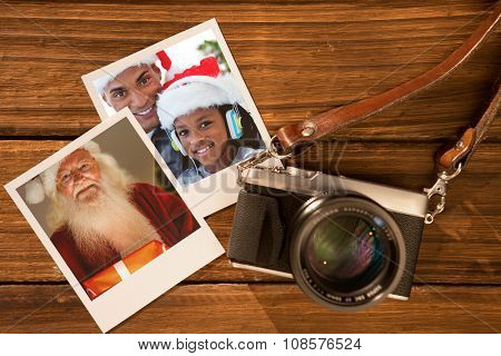 Happy santa holding a glowing gift against instant photos on wooden floor