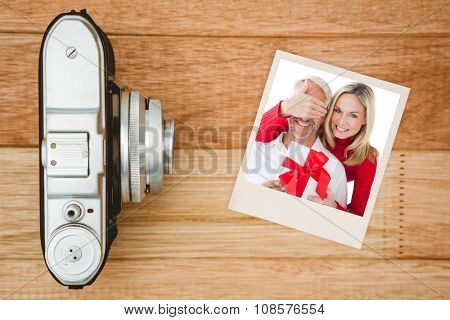 Smiling woman covering partners eyes and holding gift against view of an old camera