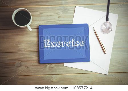 The word exercise and stethoscope against high angle view of digital tablet and document with coffee