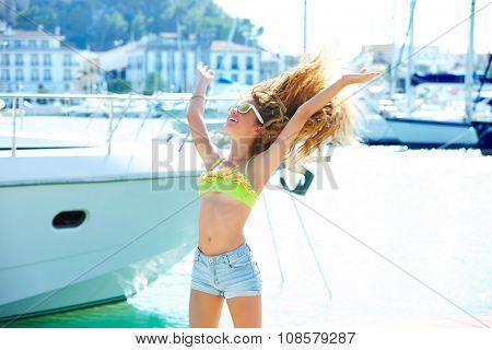 Blond kid teen girl in Mediterranean port of Spain shaking hair to wind