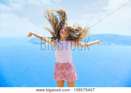 Blond girl shaking hair on air at blue Mediterranean sea tourist in Spain