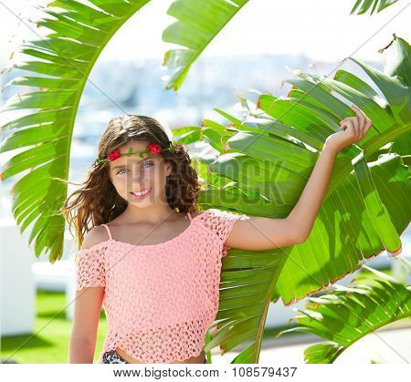 Brunette kid girl at banana tree leaves in bright day light in Mediterranean