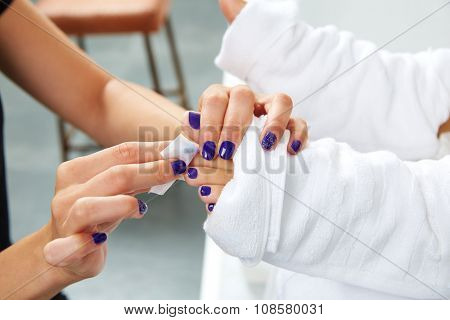 Pedicure treatment to woman feet in nails salon on sofa chair
