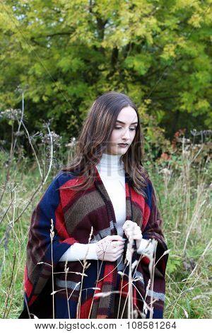 Beautiful Young Woman Walking Through A Field Of Long Grass