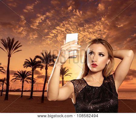 Blond tourist girl taking selfie photo Mallorca Arenal beach sunset photomount