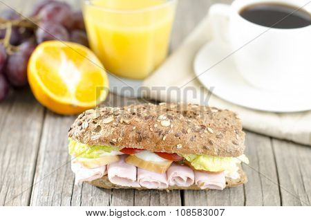Baguette on a table with croissant, nuts, orange juice, grapes with cup of coffee