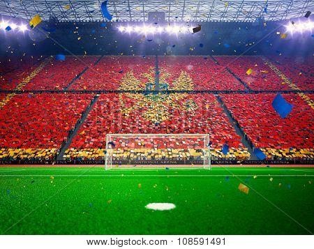 Flag Montenegro of fans. Evening stadium arena Blue