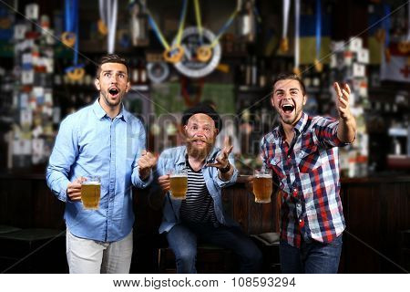 Young men with beer rejoice the victory of their favorite team in the pub