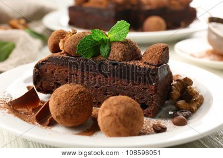 Chocolate balls, a piece of cake with walnut and mint on the table, close-up